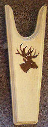 Dark Silhouette of a deer on a light unstained background wooden bootjack