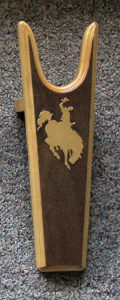 Sturdy Pine Boot Jack with a light Bucking Bronc Sillhouette on dark background from Rawhide Gifts and Gallery
