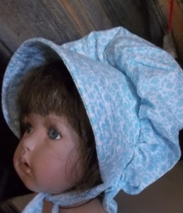 sky blue baby bonnet with dense packed flower pattern