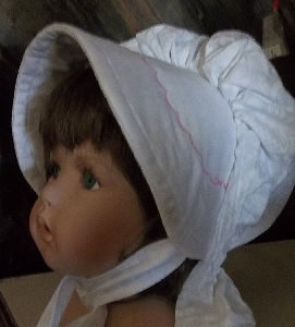 White baby bonnet with pink scalloped embroidery