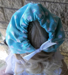 Back view of baby and infant blue polka dot bonnet